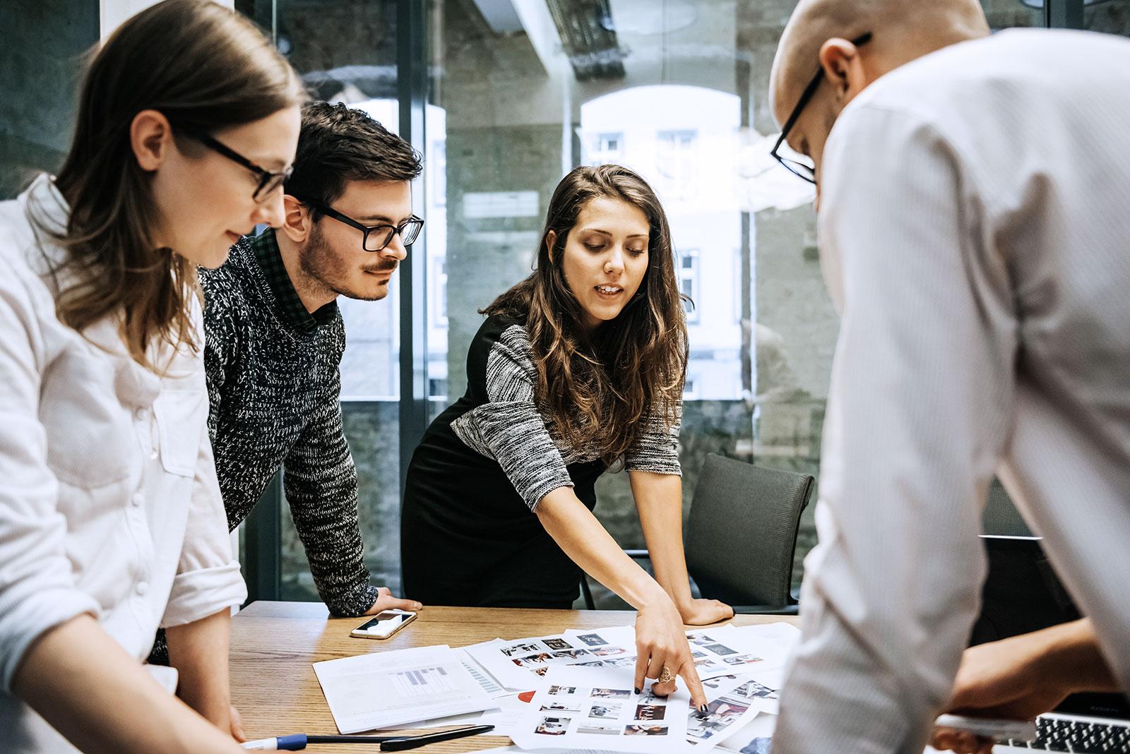 Ein Team von Mitarbeitern tauscht sich am Konferenztisch über Ideen aus: Teamwork so, wie es bisher war – aber durch die Digitalisierung in vielen Bereichen nicht mehr lange sein wird.