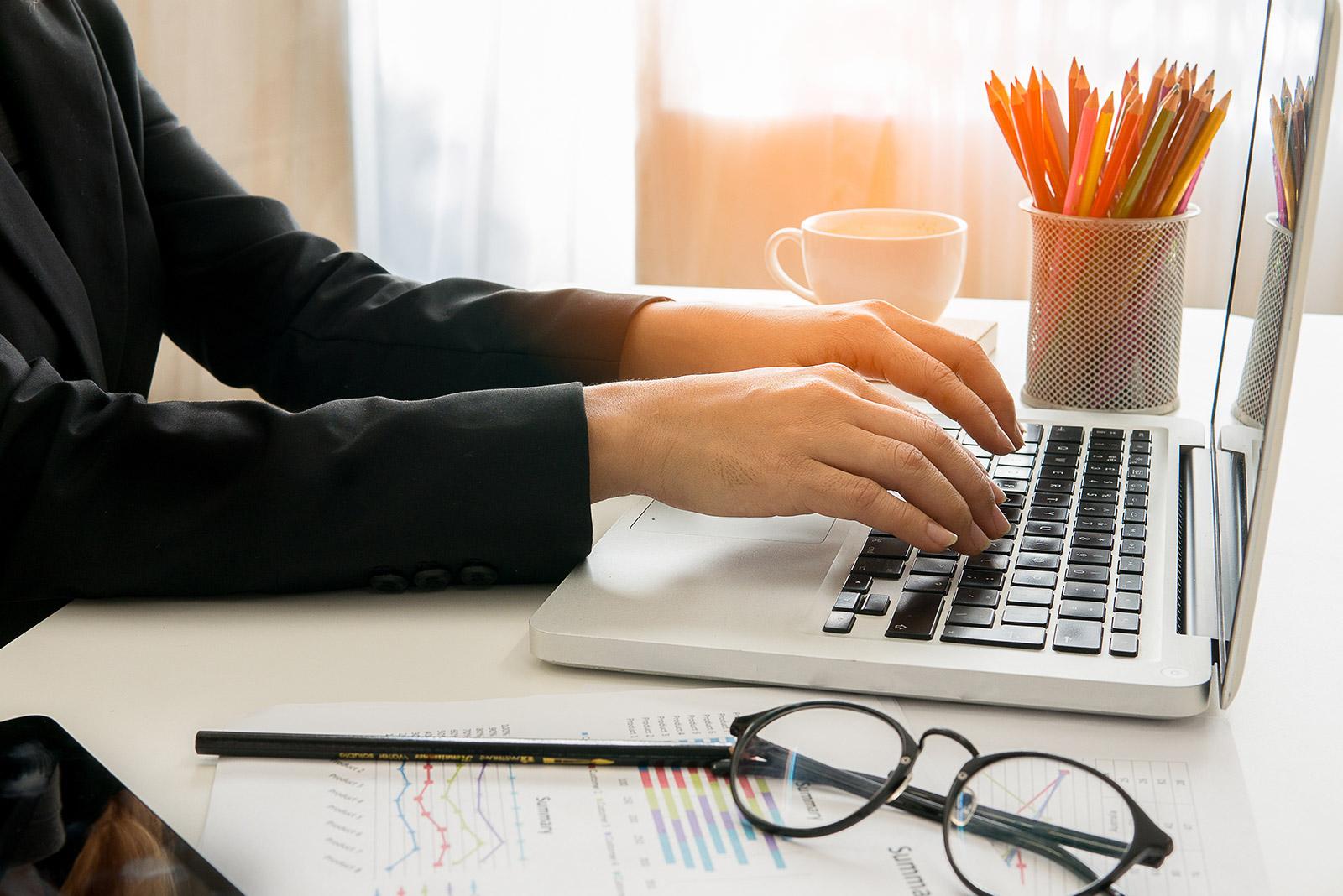 Eine Person sitzt am Schreibtisch vor einem Laptop und arbeitet.