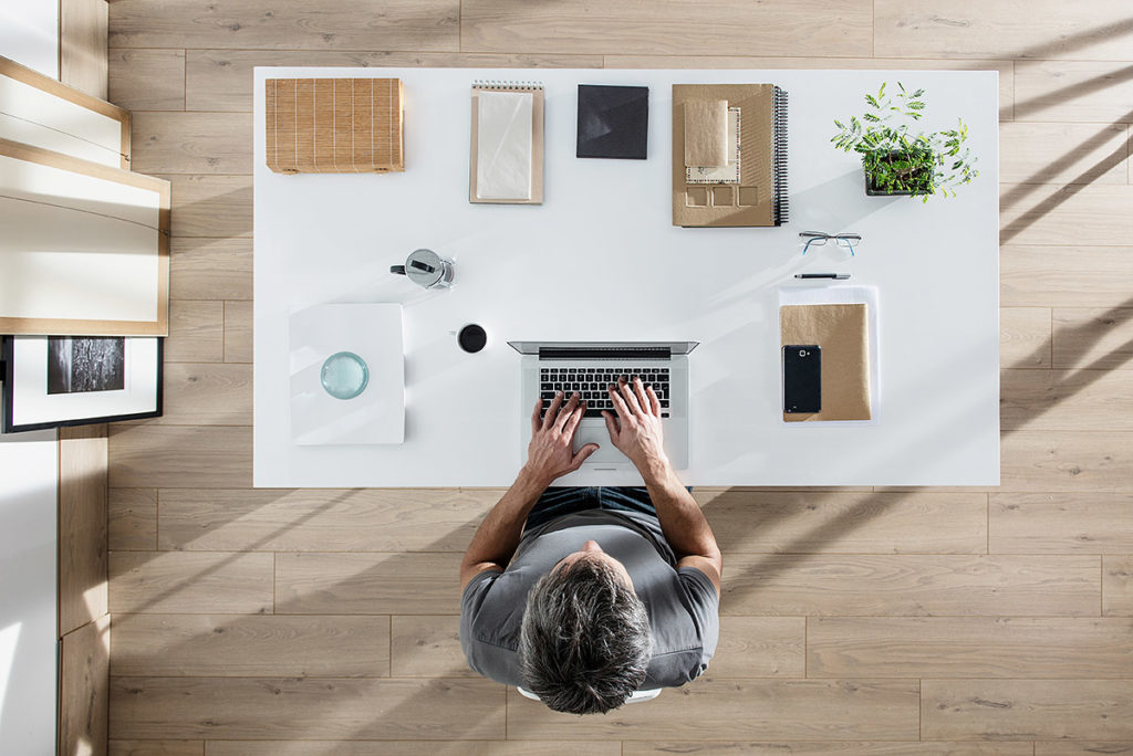 Ein Mann nutzt seinen Arbeitsplatz am Schreibtisch effizient aus