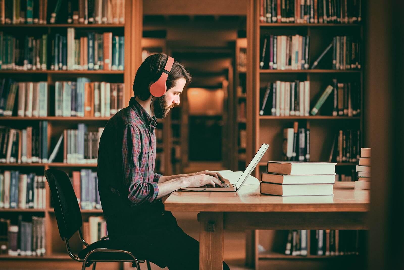 Junger Mann lernt alleine vor dem Laptop