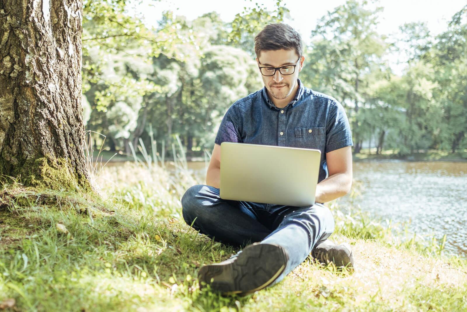 Ein Mann arbeitet im Park statt im Büro