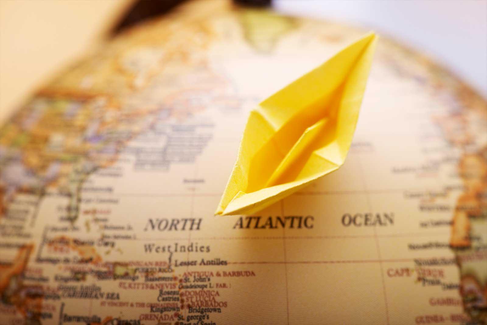 Ein Papierschiff überquert den Ozean auf einem Globus.