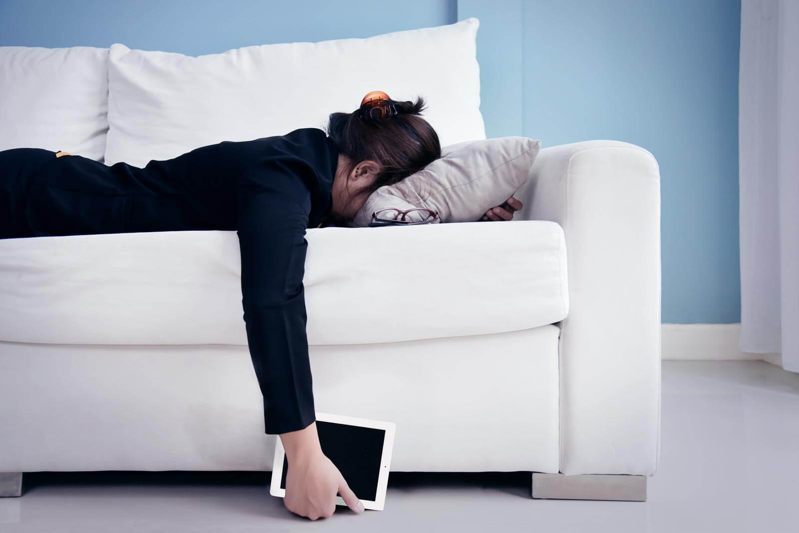 Frau liegt erschöpft auf dem Sofa mit Tablet in der Handy