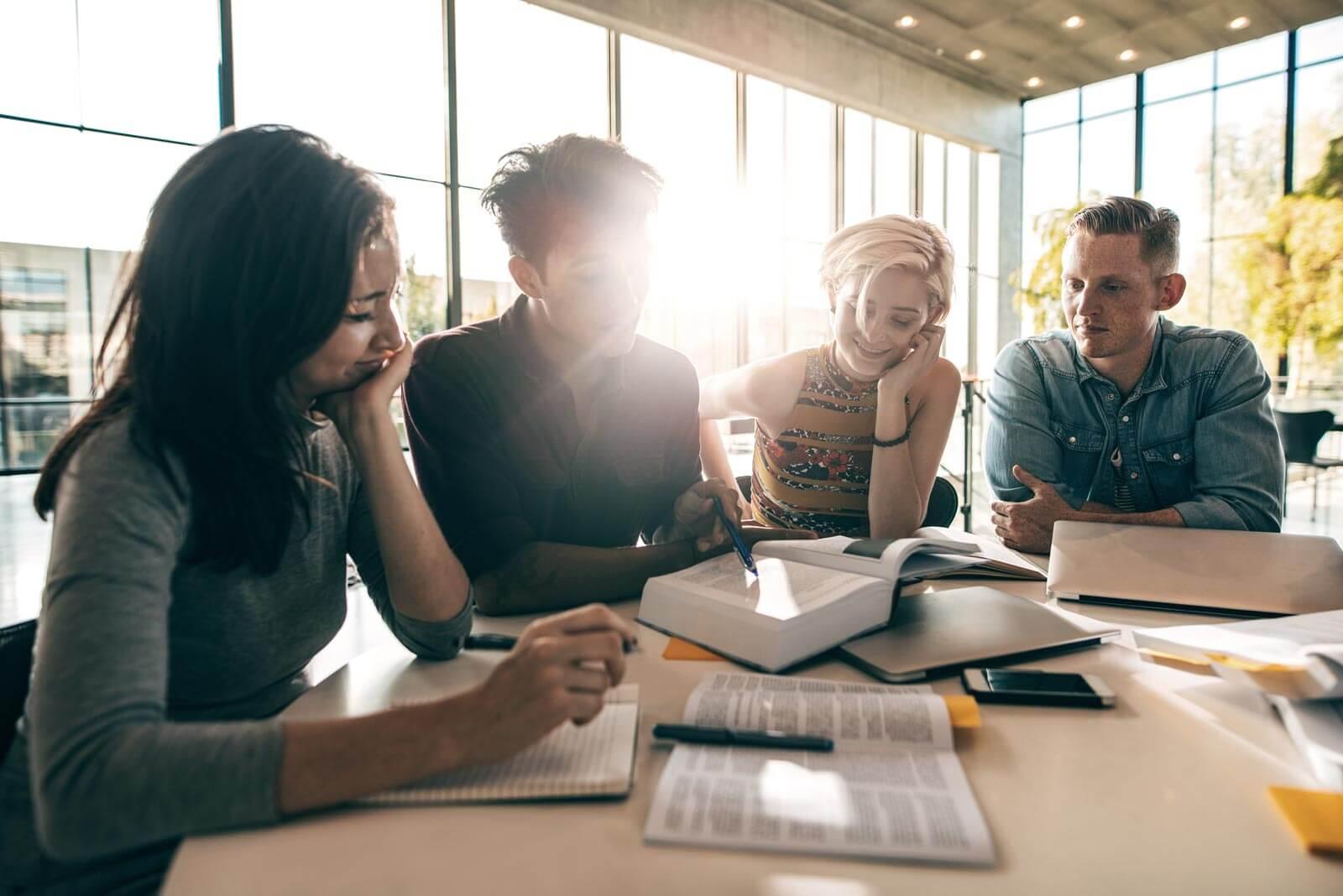 Menschen sitzen am Tisch zusammen und arbeiten
