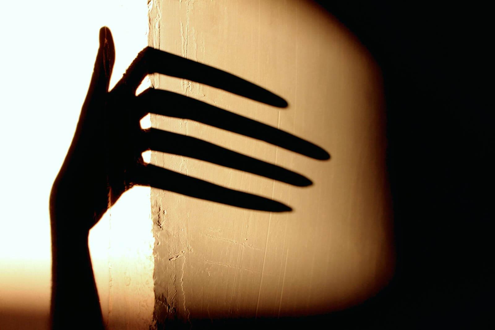 Schatten einer Hand auf einer Wand