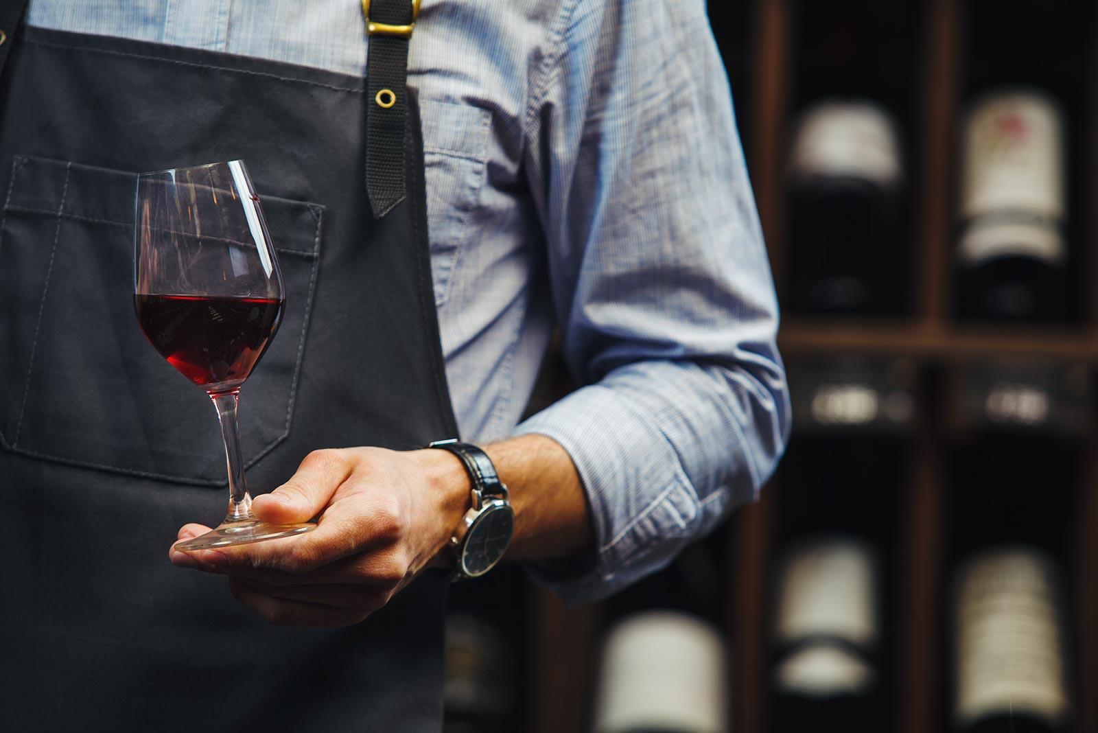 Ein Mann mit einem Glas Rotwein in der Hand