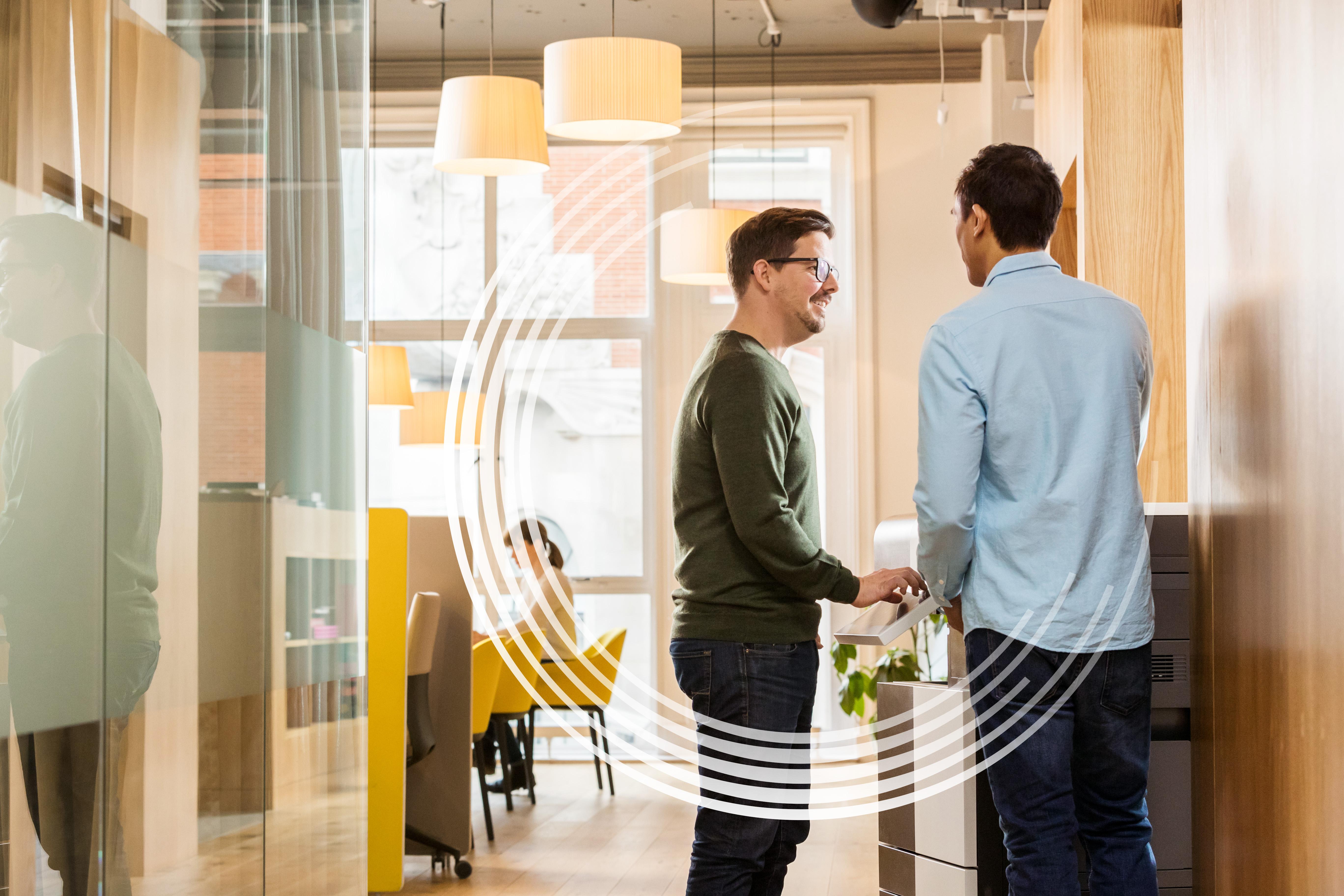 zwei Männer stehen vor einem Workplace Hub
