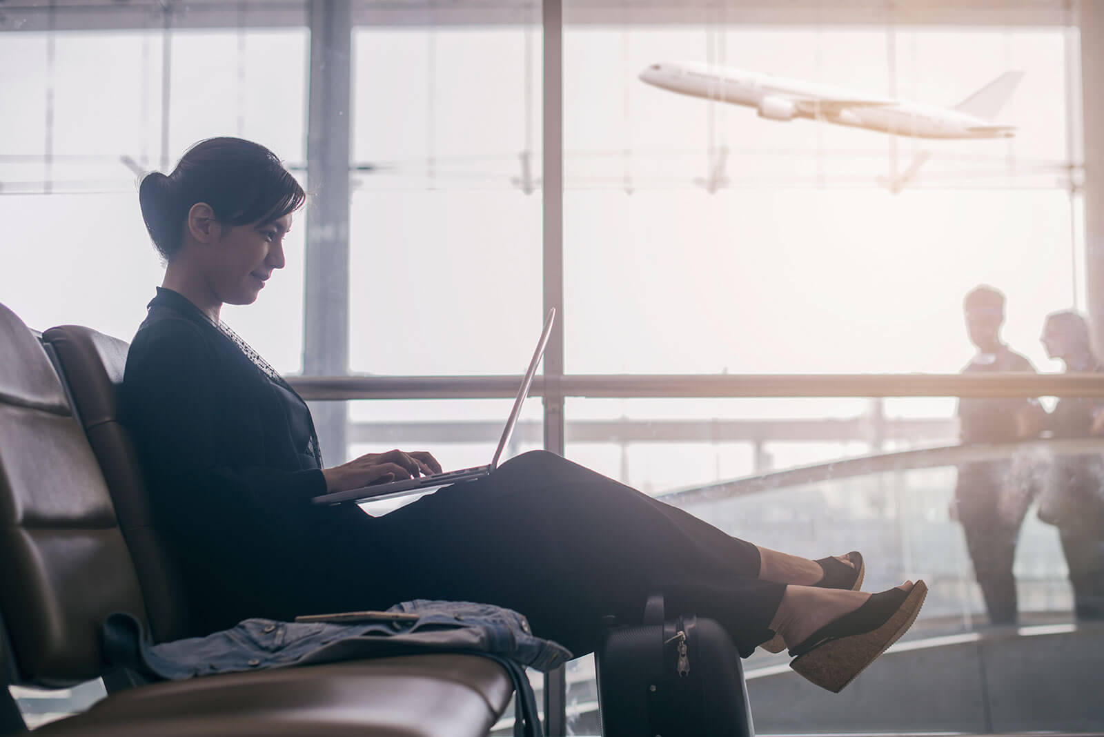 Eine Frau arbeitet am Gate und wartet auf Ihren Flug