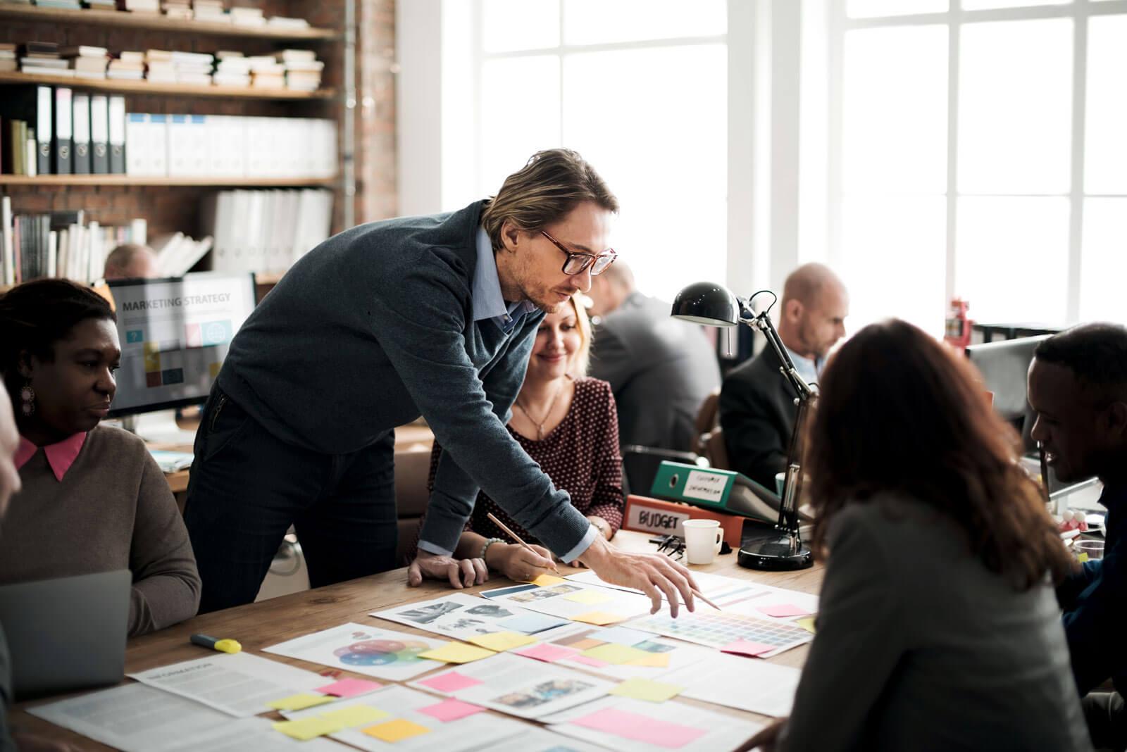 Ein Mitarbeiter erklärt seinen Kollegen etwas auf Papier, welches auf dem Tisch liegt