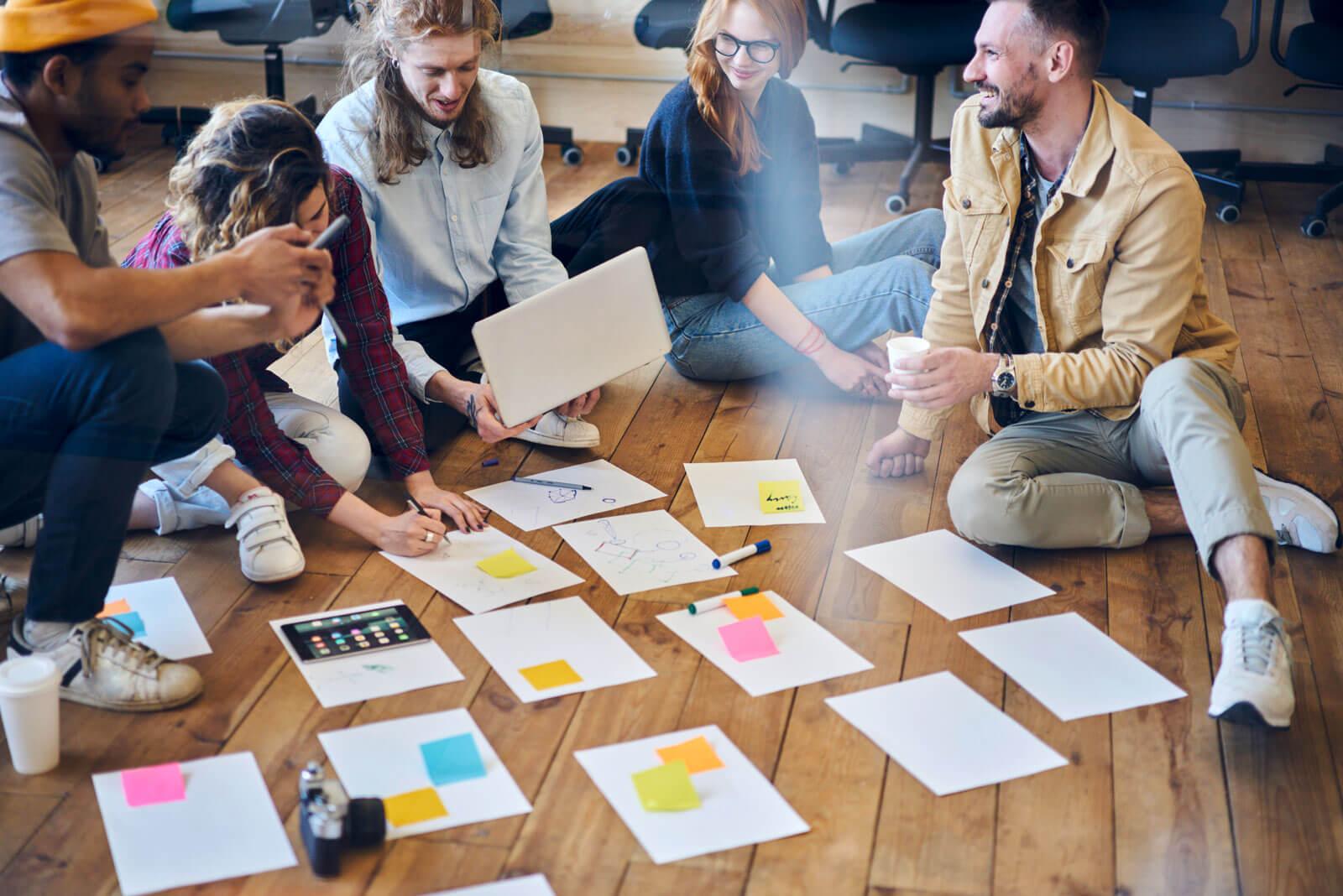 Ein Gruppe sitzt auf dem Boden und diskutiert mit Papier und Post its