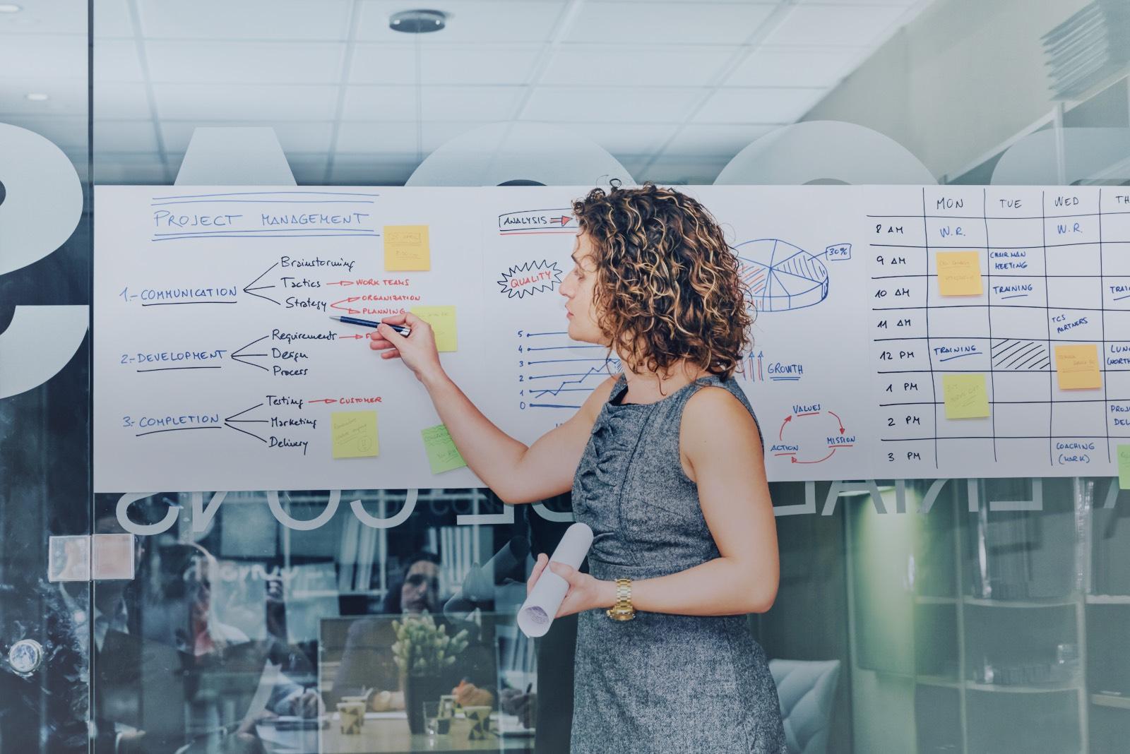 Eine Frau vor einem Managementpapier, die die nächsten Schritte zeigt.