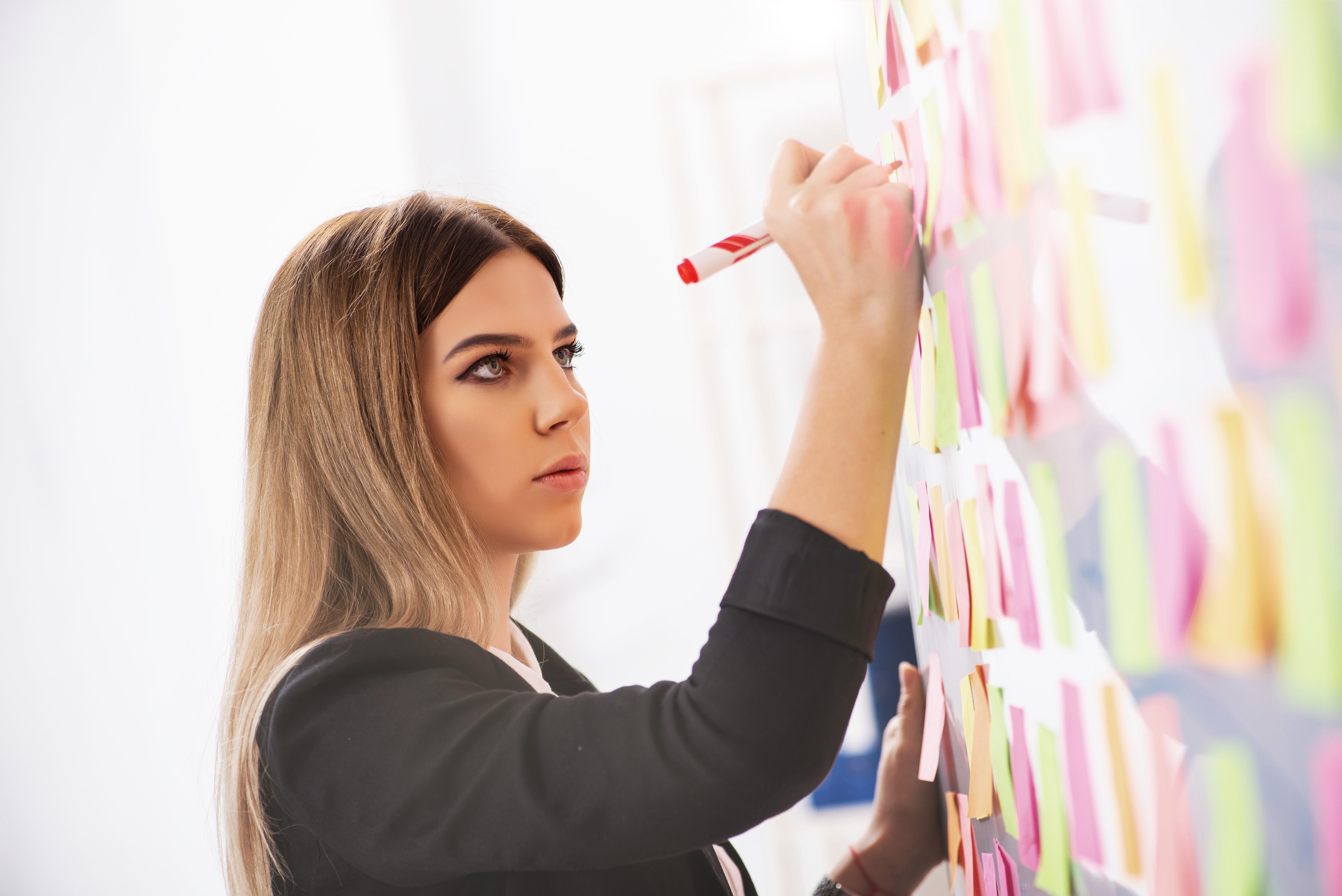Eine Frau schreibt auf Post Its an der Wand