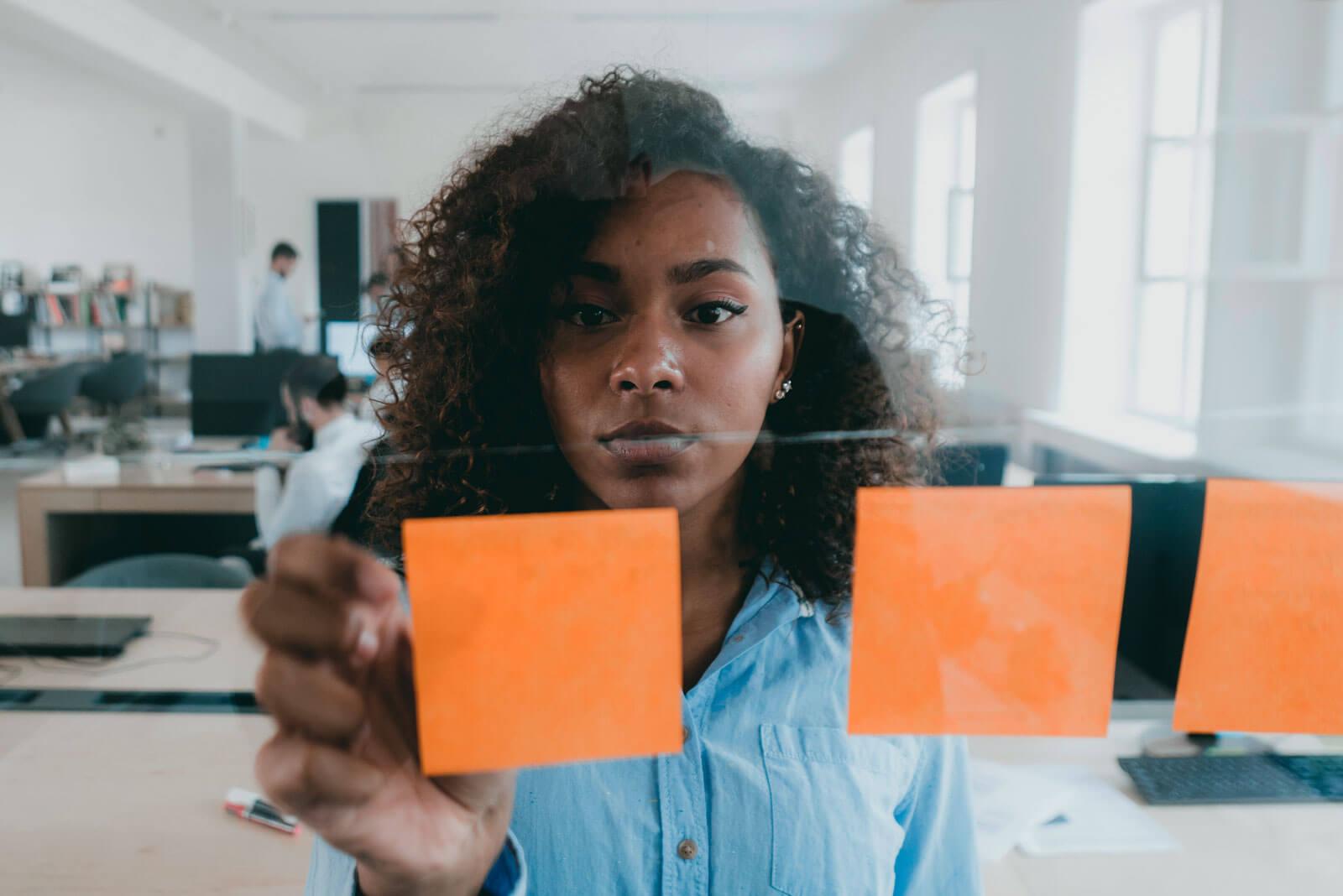 Eine Frau befestigt Post Its an einer Glaswand