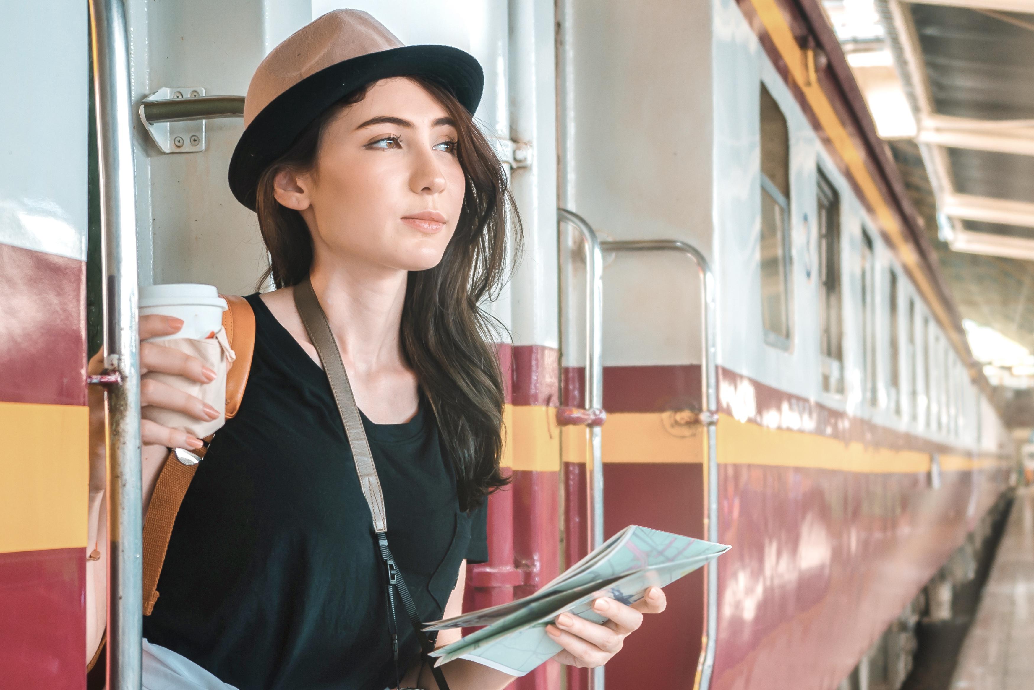 Ein Frau steht am Zug und schaut auf einen Straßenplan