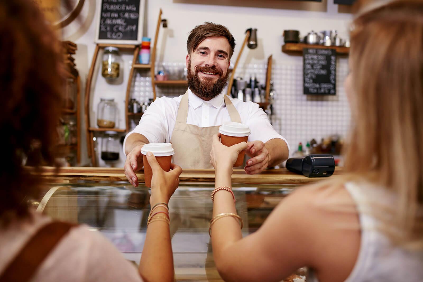 Ein Mann hinter der Theke reicht seinen Kundinnen Kaffee