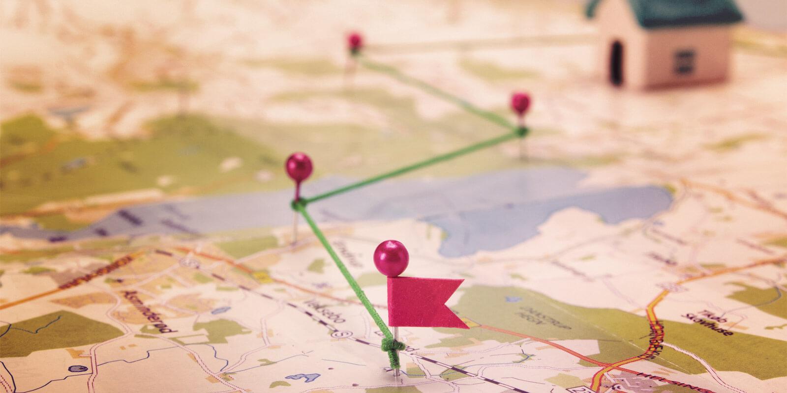 Landkarte mit Nadeln darauf, die mit einem grünen Faden miteinander verbunden sind.