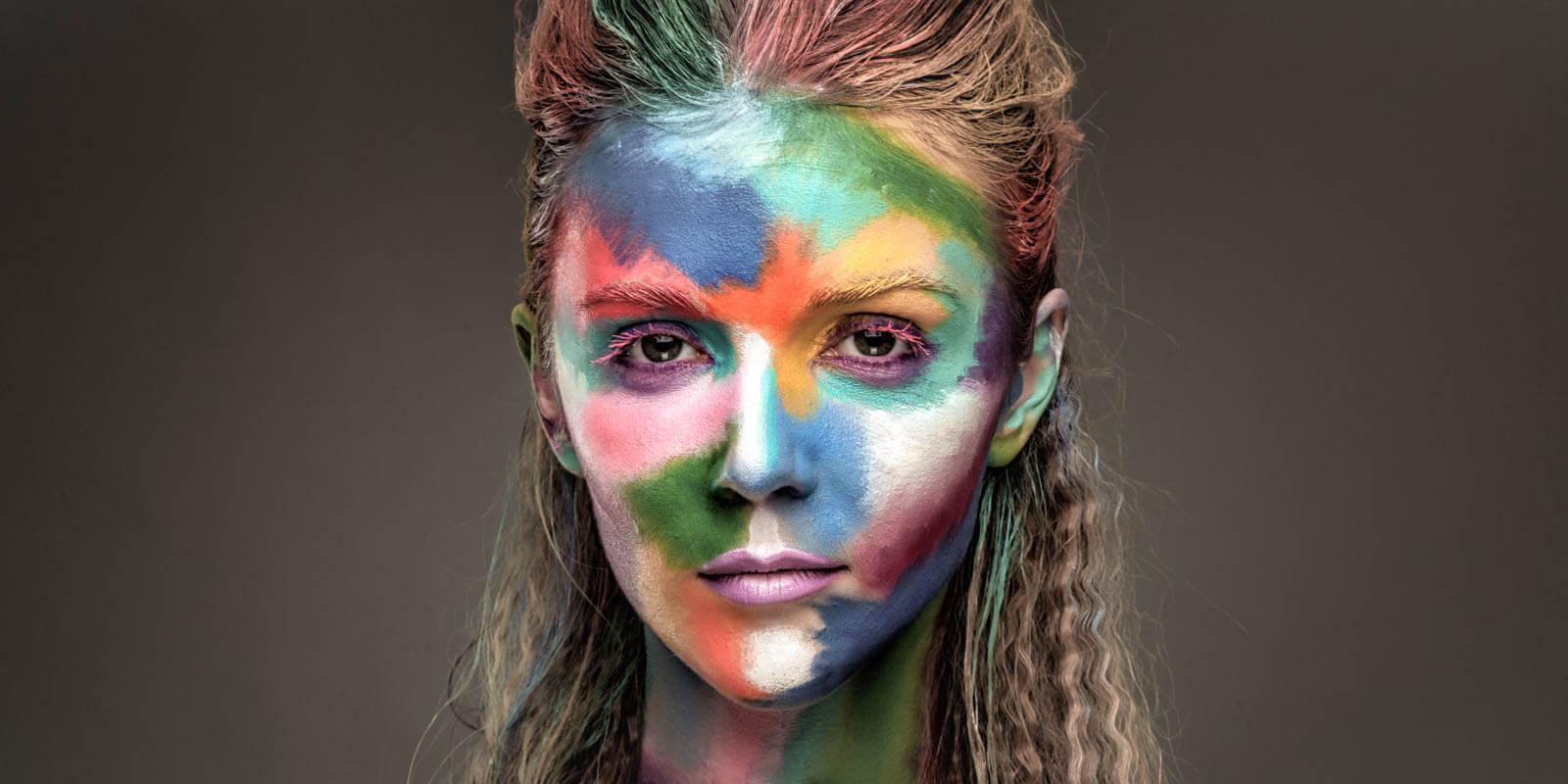 Eine Frau mit bunter Farbe im Gesicht