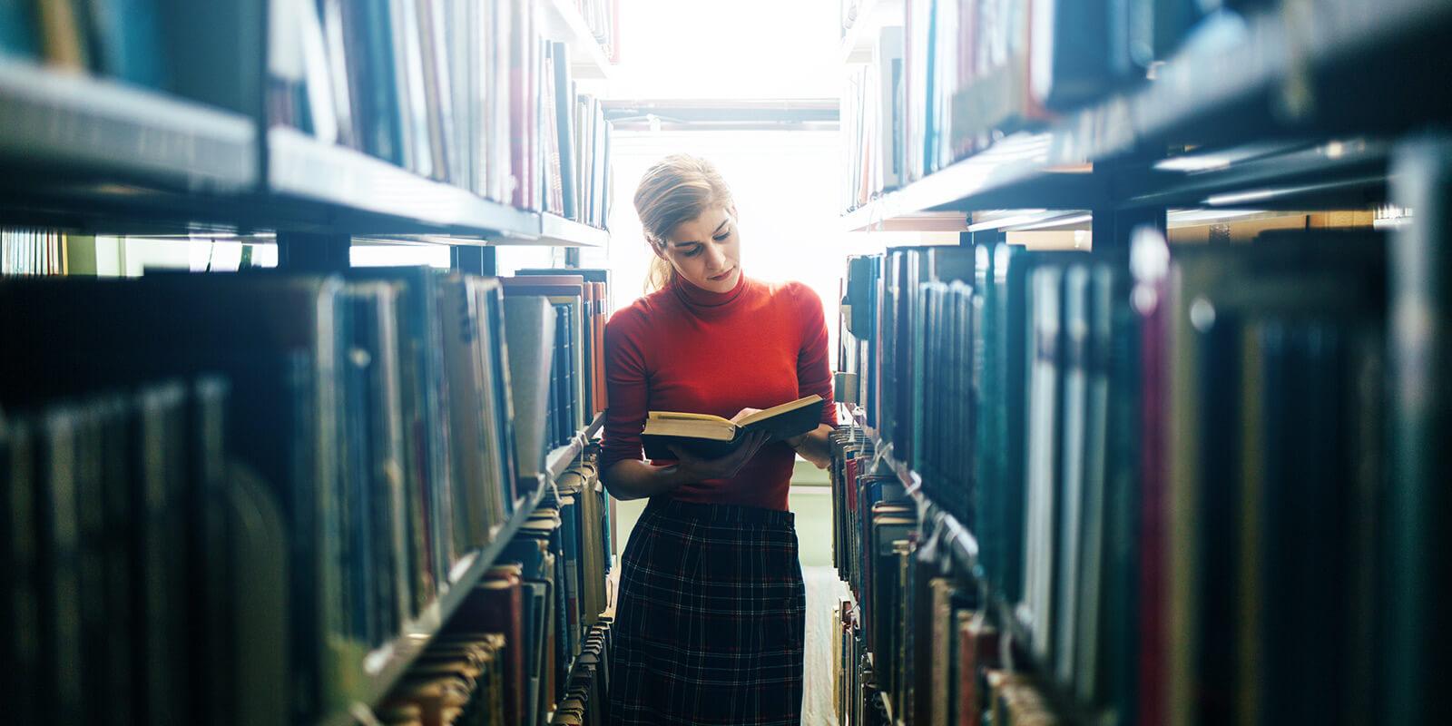 EIn Frau steht inmitten von Bücherregalen und liest