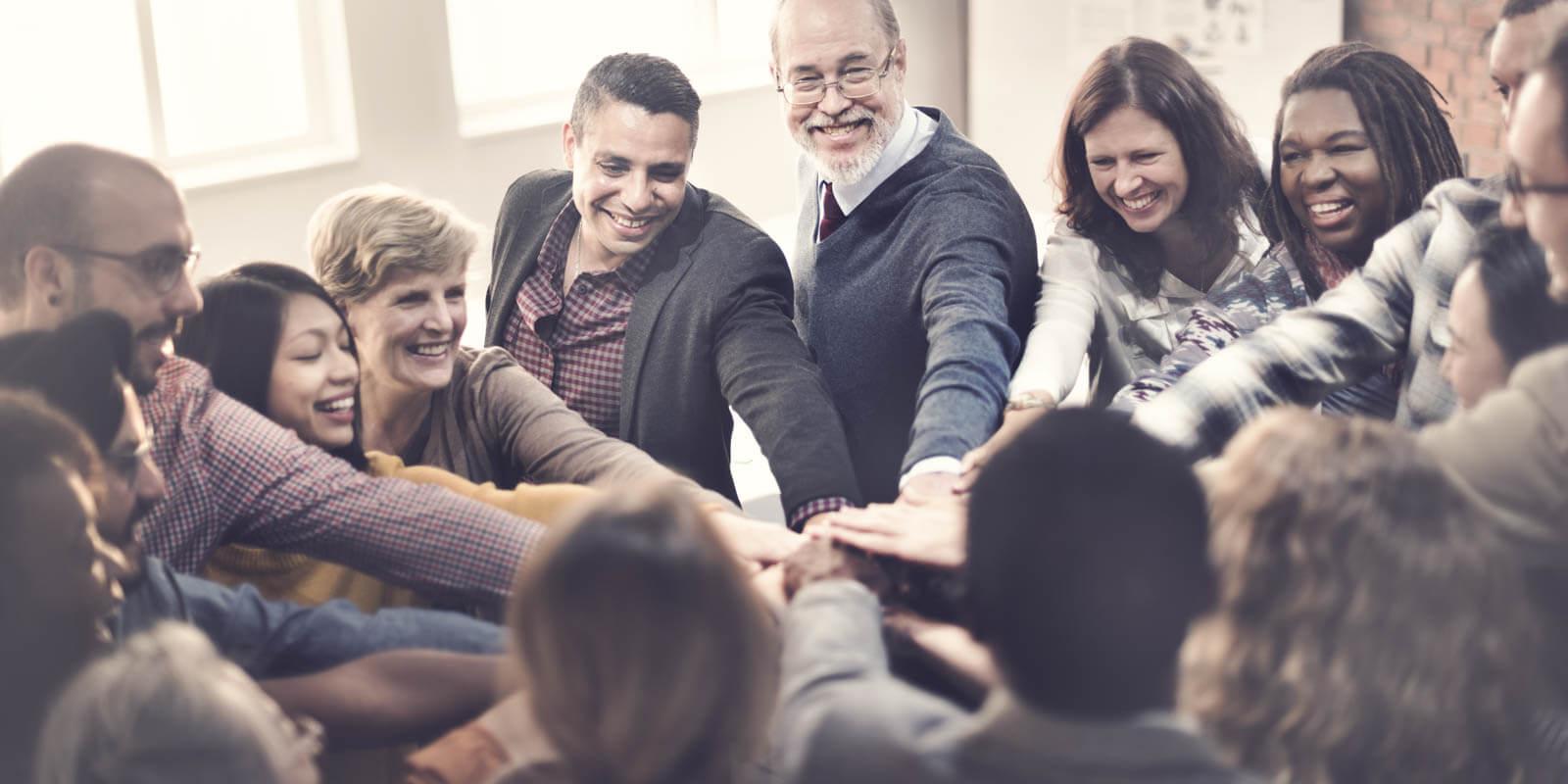 Ein Gruppe von Menschen steht im Kreis und motiviert sich selbst