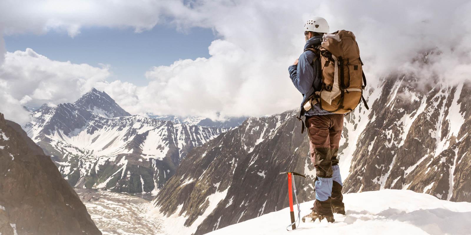 Ein Bergsteiger steht auf einem Berg und schaut in die Ferne