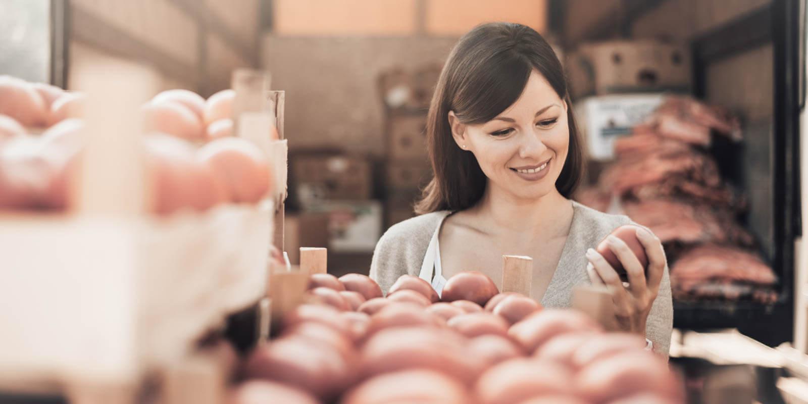 Eine Frau überprüft das gekaufte Obst, ob die Qualität stimmt