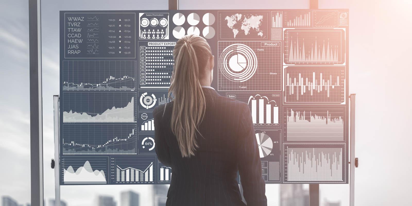 Eine Frau steht vor einer Wand mit Diagrammen und Charts um Daten zu analysieren