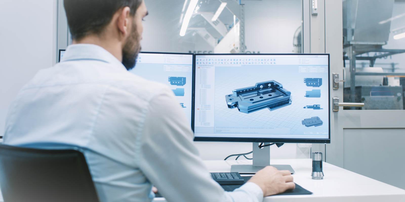 Ein Mann sitzt vor einem Computer und macht Berechnungen für einen Maschinenbauteil