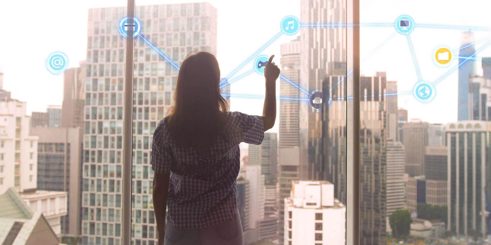 Eine Frau steht vor einem smart window und nutzt es wie einen Monitor