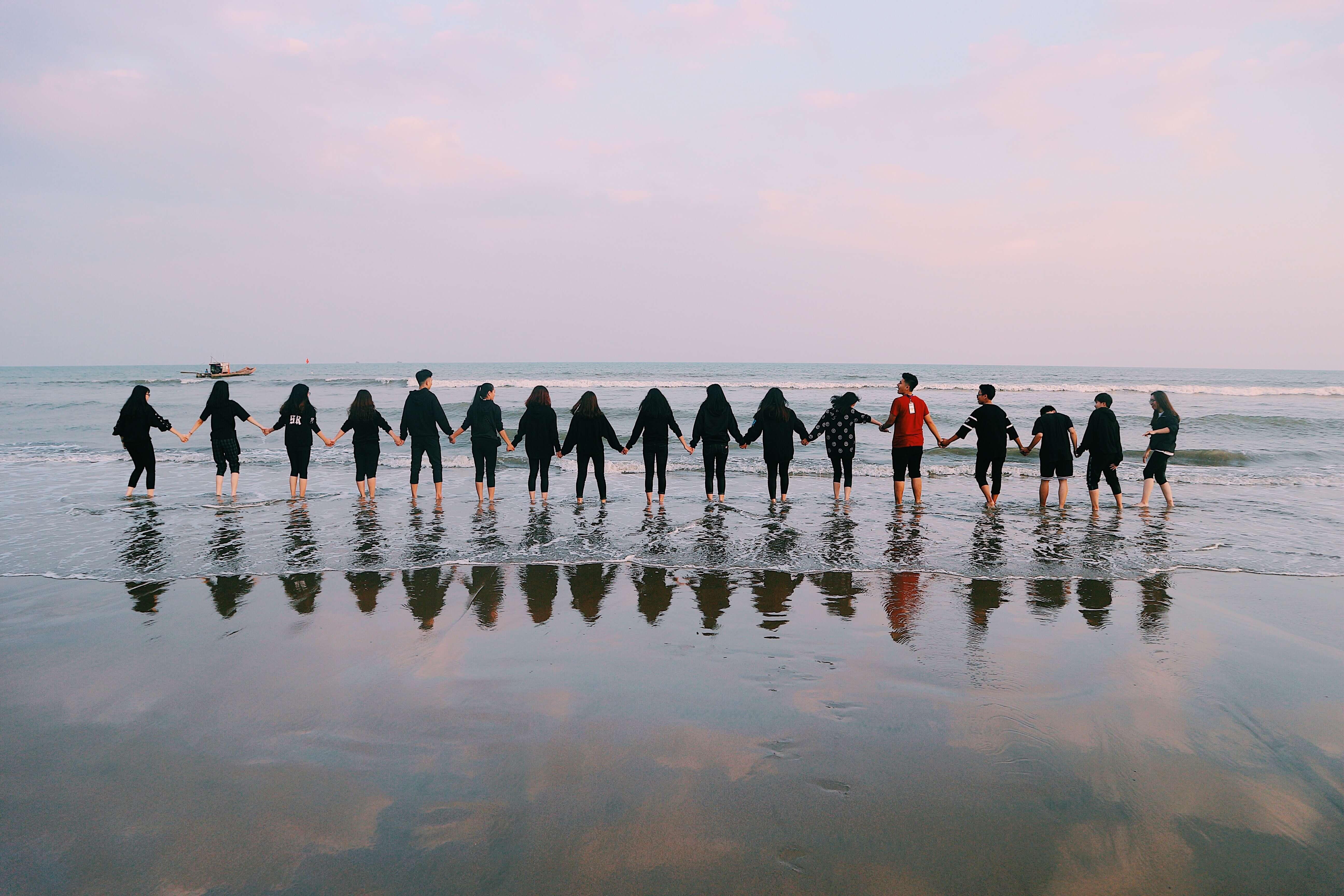 Team hält die Hände am Strand direkt am Wasser