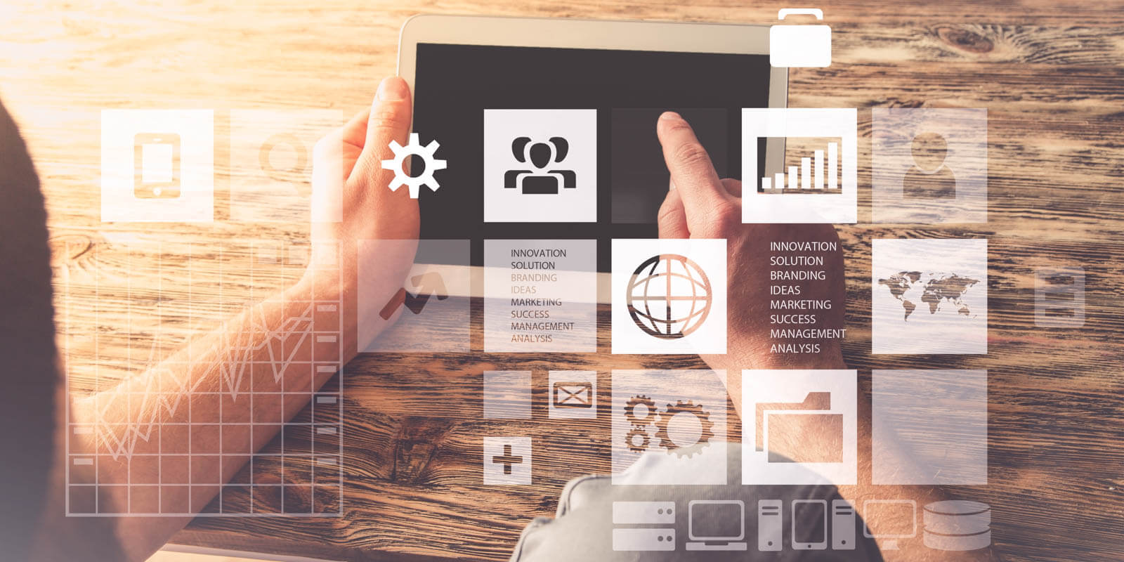 A tablet wird auf Holztisch in der Hand gehalten, darübergelegt die großen Möglichkeiten, die diese Technik bietet