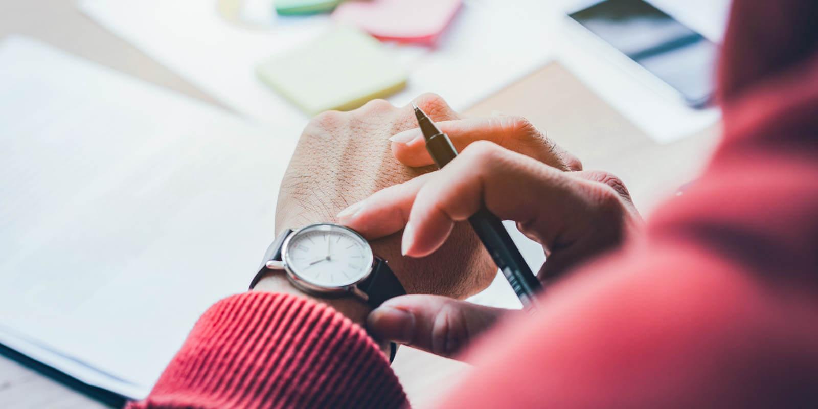 Ein Mensch mit rotem Pullover schaut auf die Armbanduhr