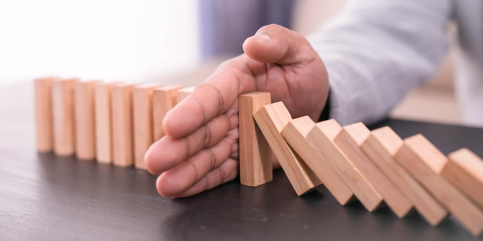 Eine Hand hält fallende Dominosteine auf