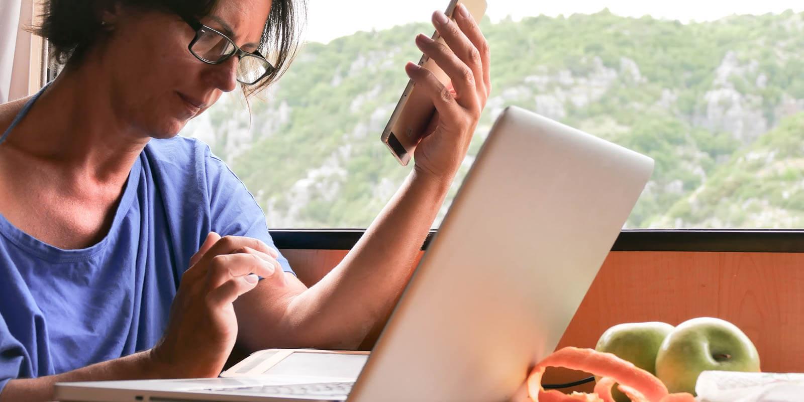 Eine Frau arbeitet von unterwegs auf verschiedenen Geräten connected