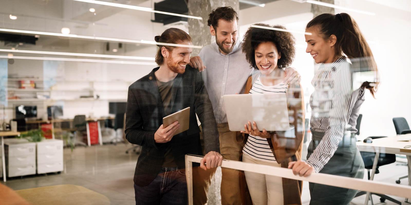 Vier Kollegen schauen gemeinsam in ihr Intranet auf dem Laptop