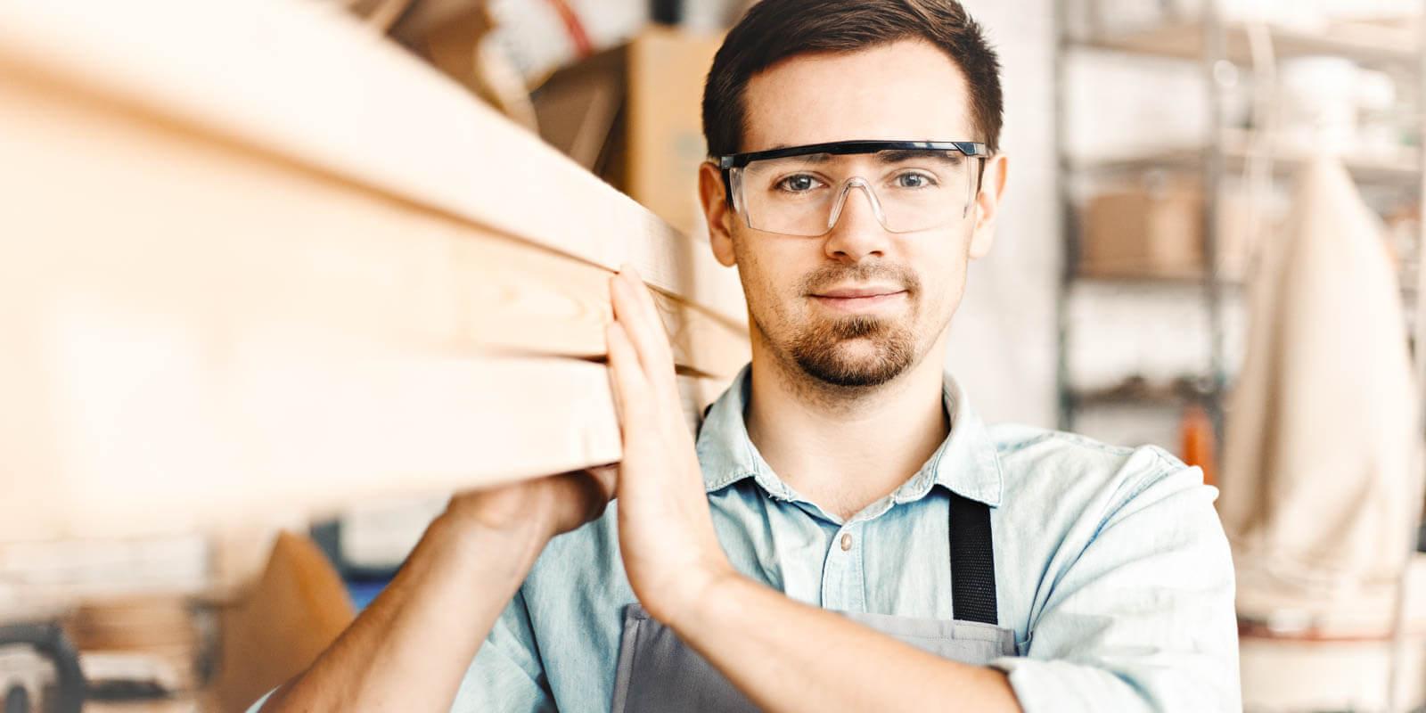 Ein Mann trägt Holzlatten