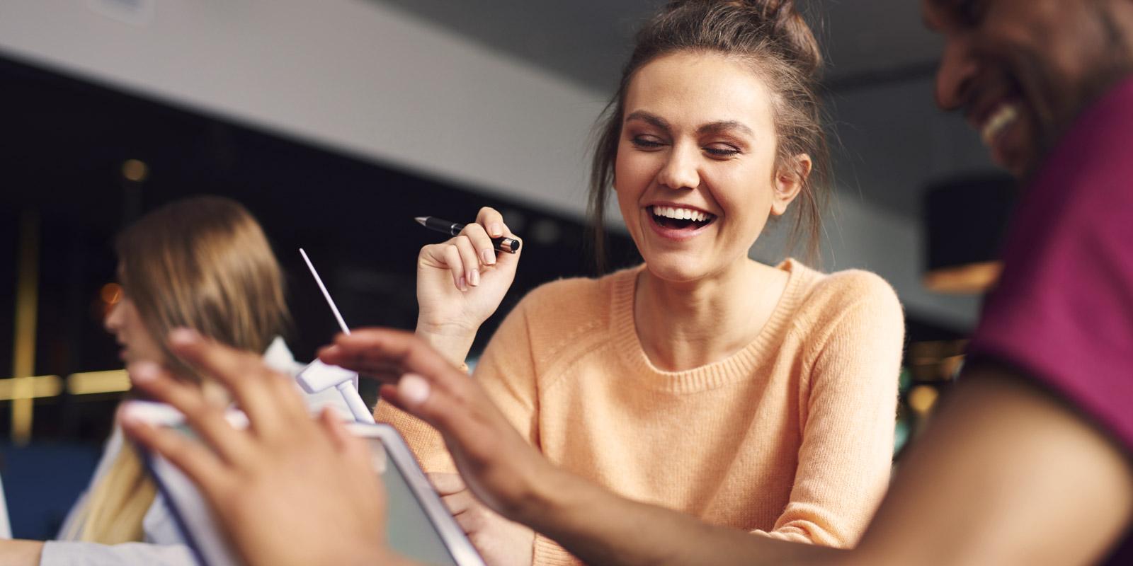 Eine junge Faru sitzt lachend am Schreibtisch