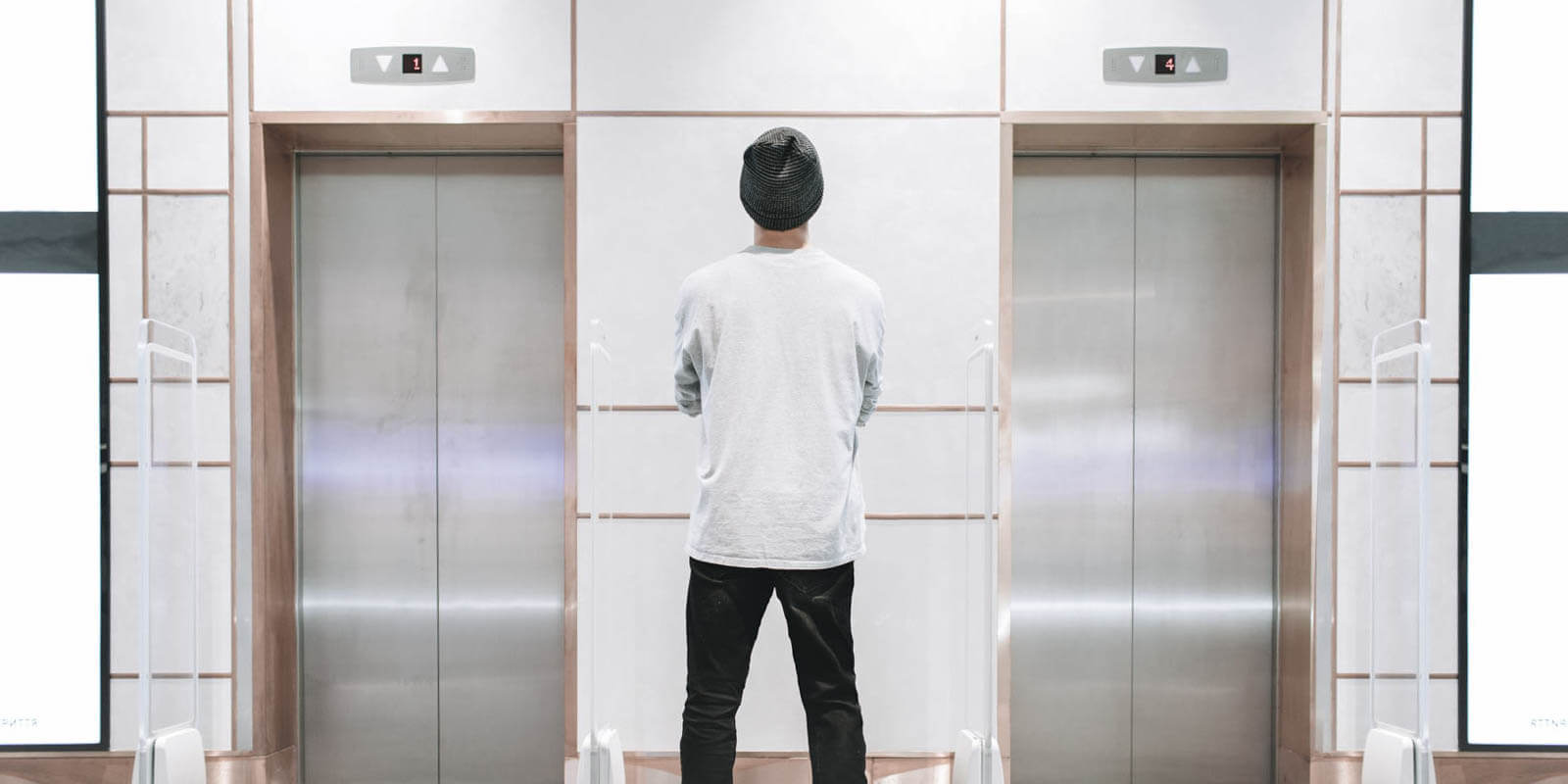 A man stands in fron of elevators, waiting to come