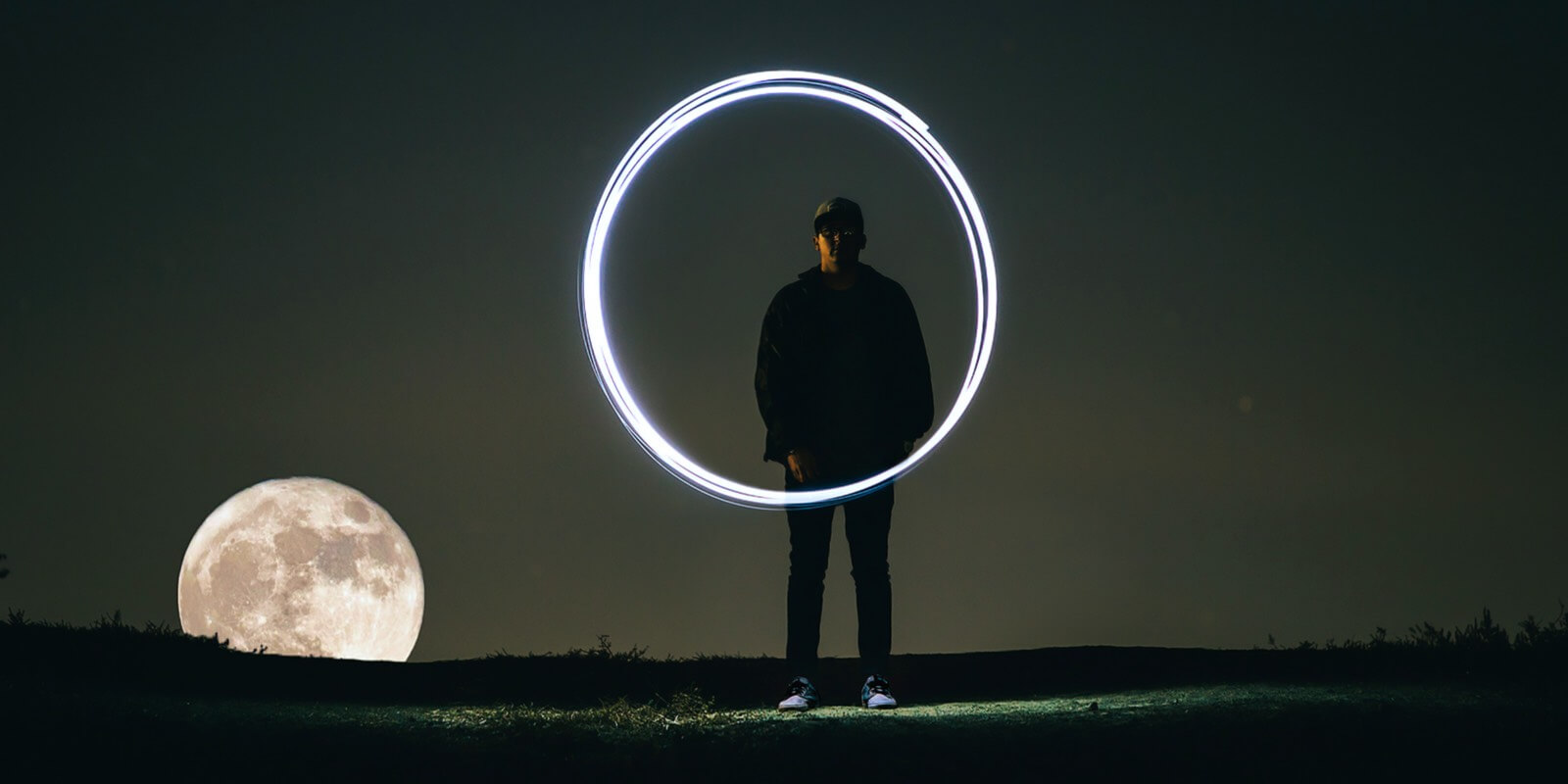 A man in the night in front of the moon makes a circle with light