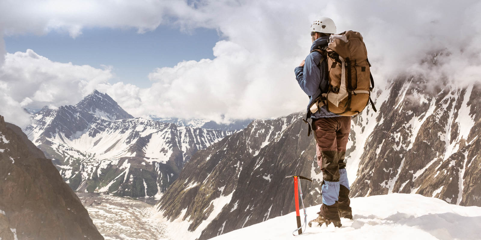 A mountaineer stands on a mountain and looks into the distance