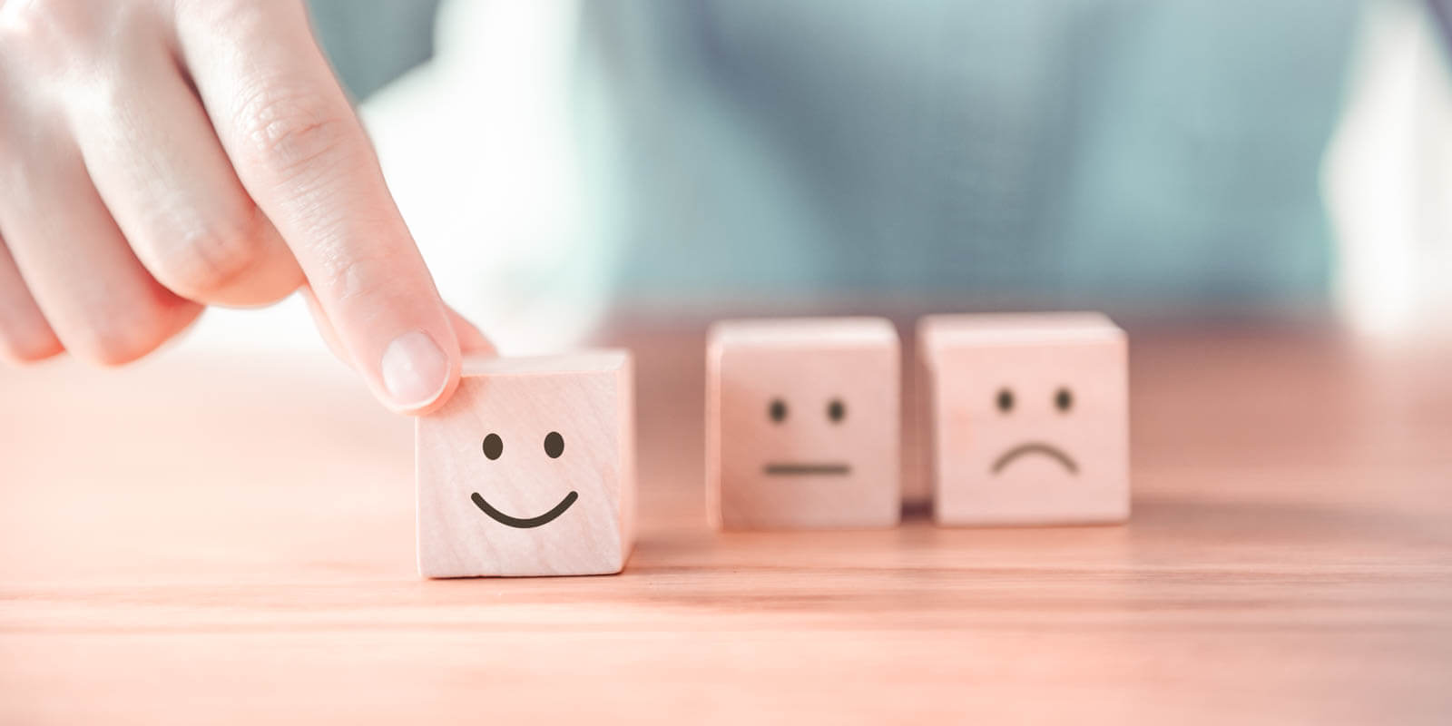 Three wooden cubes with a happy, a neutral and a sad face on it