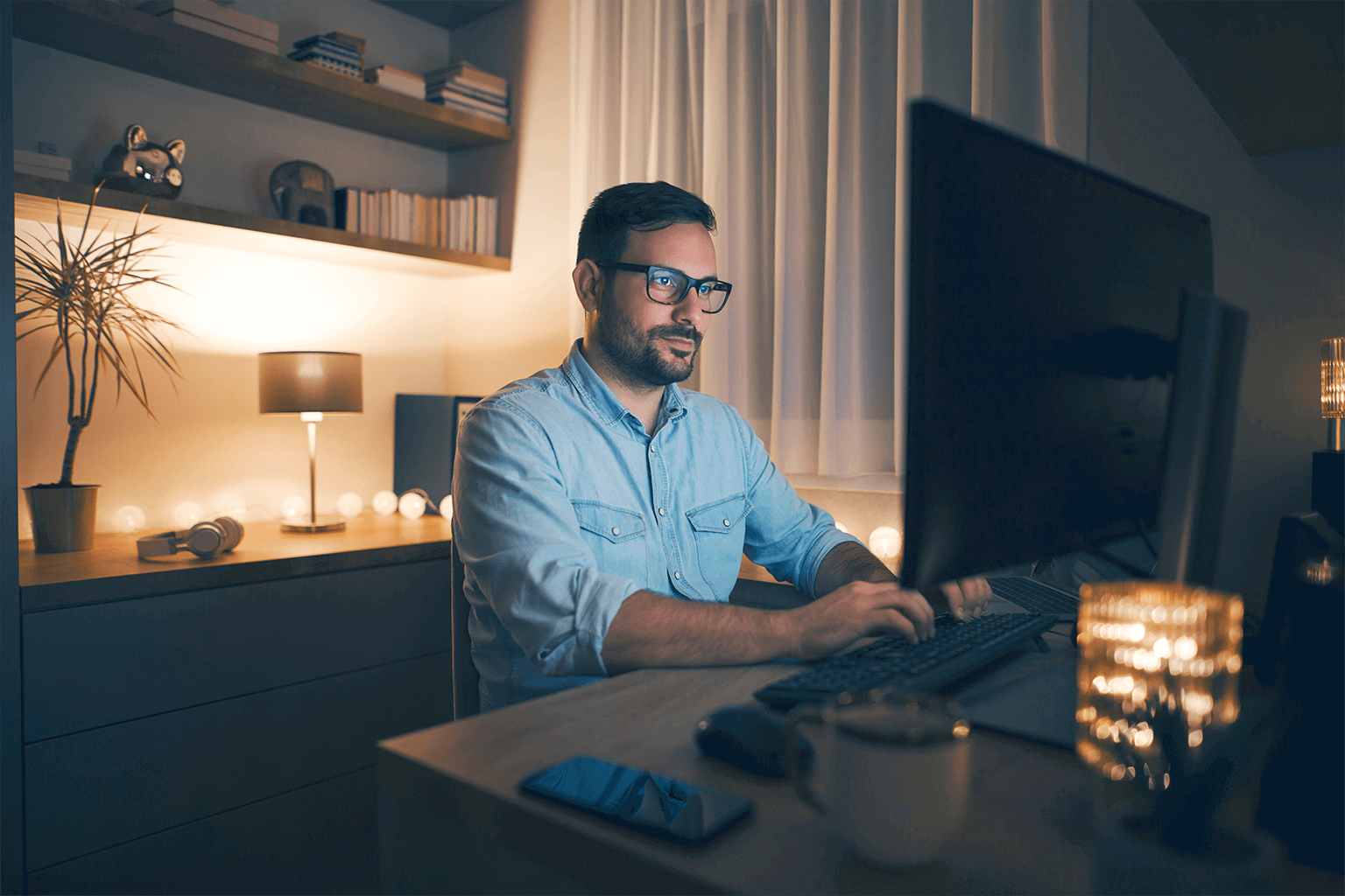 A man sits at home in front of his computer with lights on